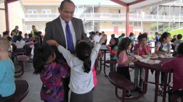 Kids run to greet Godwin Higa, principal of Cherokee Point Elementary School, during lunch.