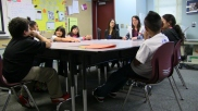 Monica Karafin (in white jacket), a San Diego State University graduate student, meets with the Pathfinders, a group of fourth and fifth graders who are learning to become peer mediators. Today, they'll do an exercise that helps them use words when it would be easier to show how to draw an image. Then they'll visit the playground, where they will eventually help mediate conflicts.