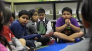 Ben, Ruby, Max, and Eduardo listen while another student talks about the problem the class is having on the playground.