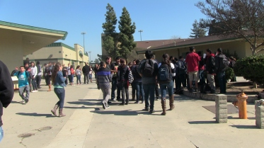 Students gather to watch two girls get in a fight. They were marched to the principal's office and then escorted off campus.