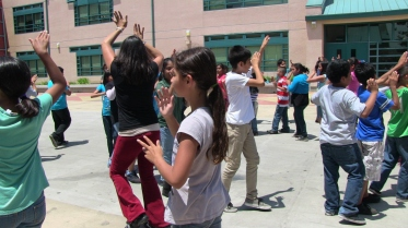 Fifth-grade students practice a dance in courtyard of Harmony Elementary School in Los Angeles, CA.