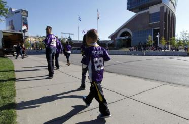 A young fan wears an Adrian Peterson jersey.  [Photo: Ann Heisenfelt/AP]